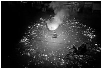 Man firing fireworks in middle of street ahead of wedding procession. Varanasi, Uttar Pradesh, India (black and white)