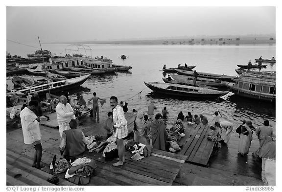 Men preparing for ritual bath on banks of Ganges River at dawn. Varanasi, Uttar Pradesh, India (black and white)