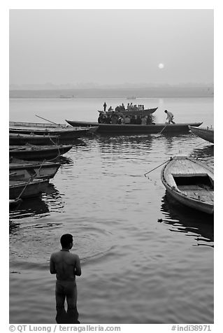 Man standing in Ganga River and boats at sunrise. Varanasi, Uttar Pradesh, India (black and white)