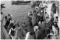 Hindu pilgrims walk out of boat onto Dasaswamedh Ghat. Varanasi, Uttar Pradesh, India (black and white)