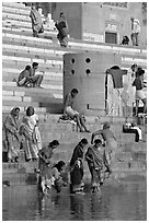 Women dipping feet in Ganga water at Sankatha Ghat. Varanasi, Uttar Pradesh, India (black and white)