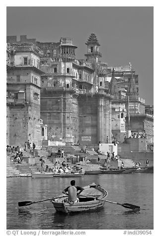 Man rowing boat beneath Munshi Ghat. Varanasi, Uttar Pradesh, India (black and white)