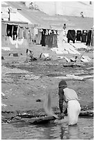 Man beating dirt out of laundry on Ganges riverbank. Varanasi, Uttar Pradesh, India (black and white)
