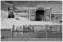 Sadhu sitting next to shrine and laundry. Varanasi, Uttar Pradesh, India (black and white)