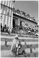Holy man sitting on temple steps, Kedar Ghat. Varanasi, Uttar Pradesh, India (black and white)
