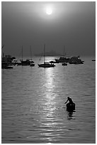 Man fishing from rowboat and anchored yachts, sunrise. Mumbai, Maharashtra, India (black and white)