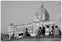 Men sitting in front of Taj Mahal Palace Hotel. Mumbai, Maharashtra, India (black and white)