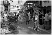 Women carrying  baskets on head in narrow street, Colaba Market. Mumbai, Maharashtra, India (black and white)
