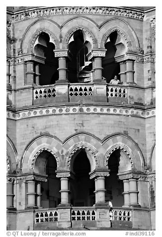 Facade with woman at window, Chhatrapati Shivaji Terminus. Mumbai, Maharashtra, India (black and white)