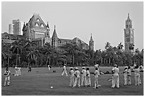 Boys in cricket attire on Oval Maidan, High Court, and Rajabai Tower. Mumbai, Maharashtra, India (black and white)
