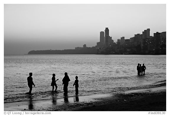 People standing in water at sunset with skyline behind, Chowpatty Beach. Mumbai, Maharashtra, India (black and white)