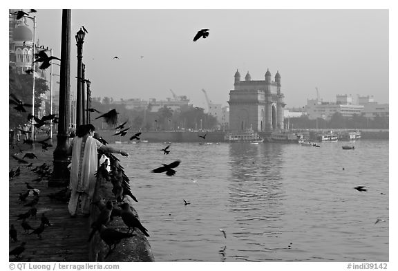 Woman feeding birds, with Gateway of India in background, early morning. Mumbai, Maharashtra, India (black and white)