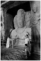 Woman and children standing in front of Mahesh Murti, main  Elephanta cave. Mumbai, Maharashtra, India (black and white)