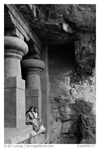 Women sitting at entrance of cave, Elephanta Island. Mumbai, Maharashtra, India (black and white)
