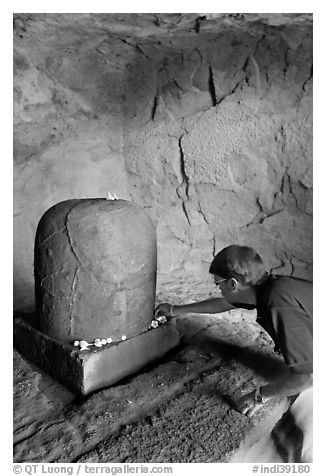 Man venerating a Linga in Shiva shrine, Elephanta Island. Mumbai, Maharashtra, India (black and white)
