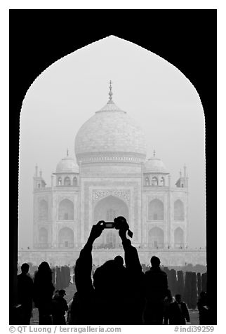 Tourist pointing  digital camera to Maj Mahal, framed by arch of gateway. Agra, Uttar Pradesh, India (black and white)