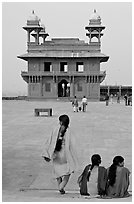 Women, Pachisi courtyard, and Diwan-i-Khas. Fatehpur Sikri, Uttar Pradesh, India (black and white)