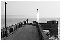 Pier with man fishing, early morning, Dona Paula. Goa, India ( black and white)