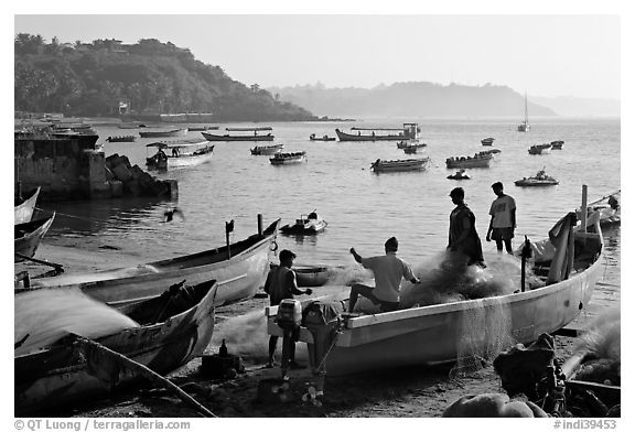 Men repairing net in small fishing boat, early morning, Dona Paula. Goa, India (black and white)