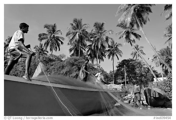 Men mending fishing net with palm trees in background. Goa, India (black and white)