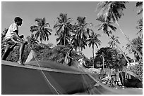 Men mending fishing net with palm trees in background. Goa, India ( black and white)