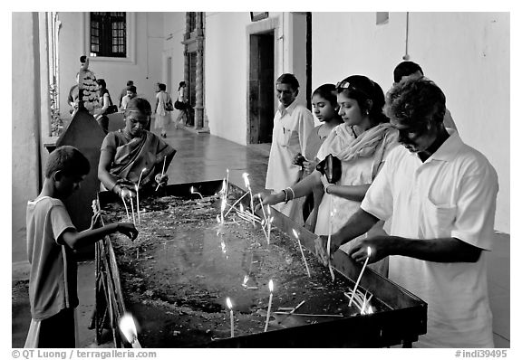 Indian people burning candles, Basilica of Bom Jesus, Old Goa. Goa, India (black and white)