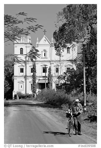 Man walking a bicycle in front of church of St John, Old Goa. Goa, India (black and white)