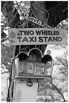 Two wheeler taxi stand and altar on tree. Goa, India ( black and white)
