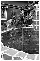 Woman retrieving water from well, Panaji. Goa, India ( black and white)