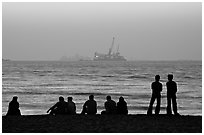 People and  off-shore platforms, Miramar Beach, sunset. Goa, India ( black and white)