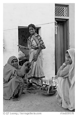 Women cooking outside in village. Khajuraho, Madhya Pradesh, India (black and white)