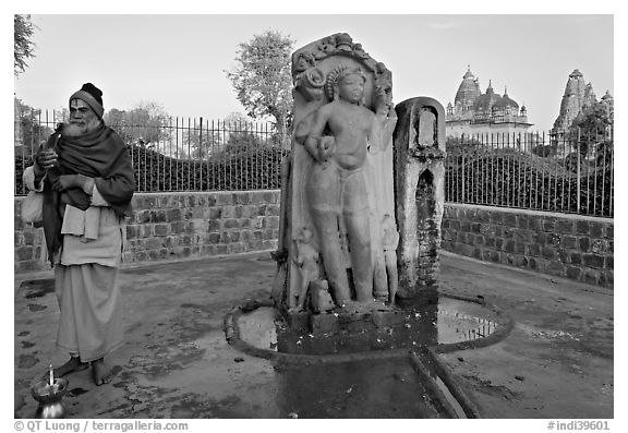 Holy man next to Shiva image. Khajuraho, Madhya Pradesh, India (black and white)