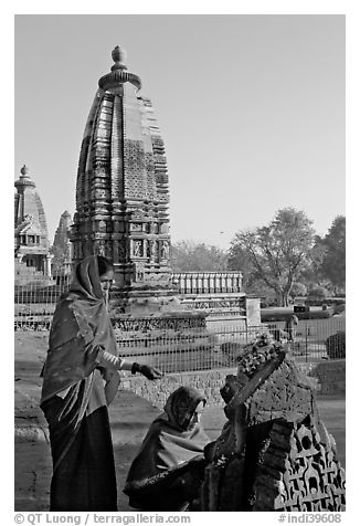 Women worshipping image with temple spire behind. Khajuraho, Madhya Pradesh, India (black and white)