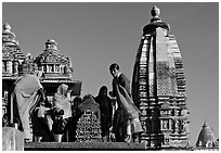 Women worshipping image with of Vahara and Lakshmana temples behind. Khajuraho, Madhya Pradesh, India (black and white)