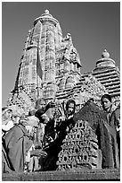 Hindu worshippers making offerings with Lakshmana temple behind. Khajuraho, Madhya Pradesh, India (black and white)