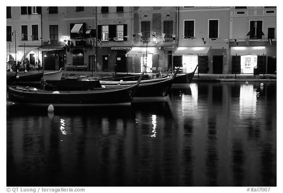 Light of shops reflected in harbor at dusk, Portofino. Liguria, Italy (black and white)