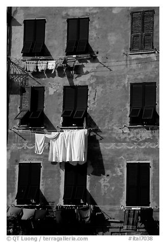 Typical terra cotta facade with hanging laundry and green shutters, Vernazza. Cinque Terre, Liguria, Italy (black and white)