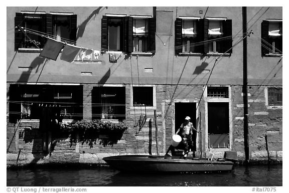 Resident stepping from his boat to his house,  Castello. Venice, Veneto, Italy (black and white)