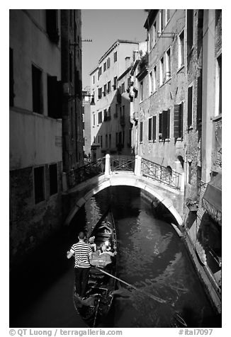 Gondola tour in a picturesque canal with bridge. Venice, Veneto, Italy (black and white)