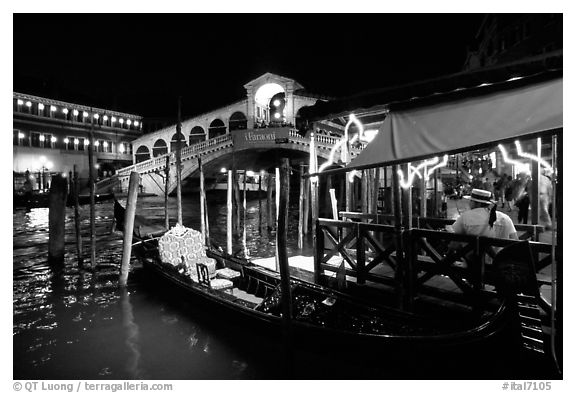 Gondolier and gondola, Rialto Bridge at night. Venice, Veneto, Italy (black and white)