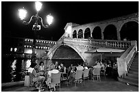 Outdoor cafe terrace,  Rialto Bridge at night. Venice, Veneto, Italy (black and white)