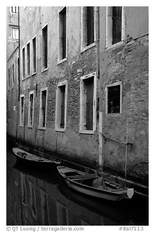 Small boats moored along a wall in a small side canal. Venice, Veneto, Italy (black and white)