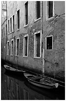 Small boats moored along a wall in a small side canal. Venice, Veneto, Italy ( black and white)