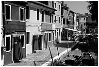 Canal bordered by multicolored  houses, Burano. Venice, Veneto, Italy (black and white)