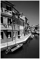 Canal surrounded by houses painted  a multitude of bright colors, Burano. Venice, Veneto, Italy ( black and white)