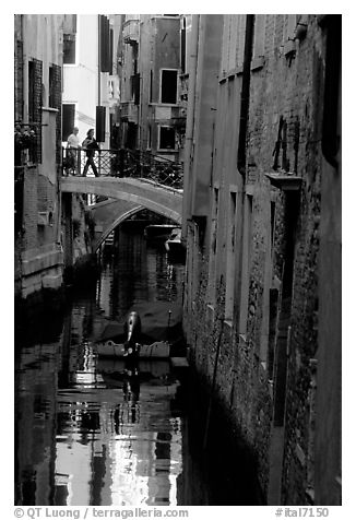 Pedestrians on a bridge over a narrow canal. Venice, Veneto, Italy (black and white)