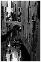 Pedestrians on a bridge over a narrow canal. Venice, Veneto, Italy ( black and white)