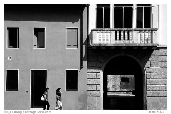 House facades with women walking. Veneto, Italy (black and white)