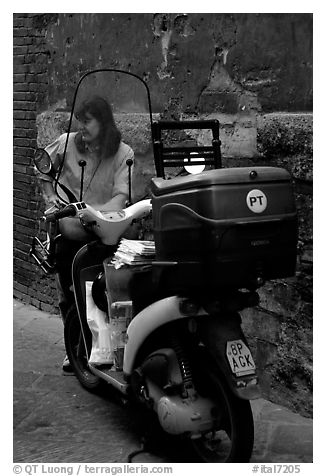 Delivering mail from a scooter. Siena, Tuscany, Italy (black and white)