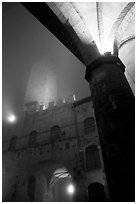 Medieval towers above Piazza del Duomo, foggy night. San Gimignano, Tuscany, Italy (black and white)